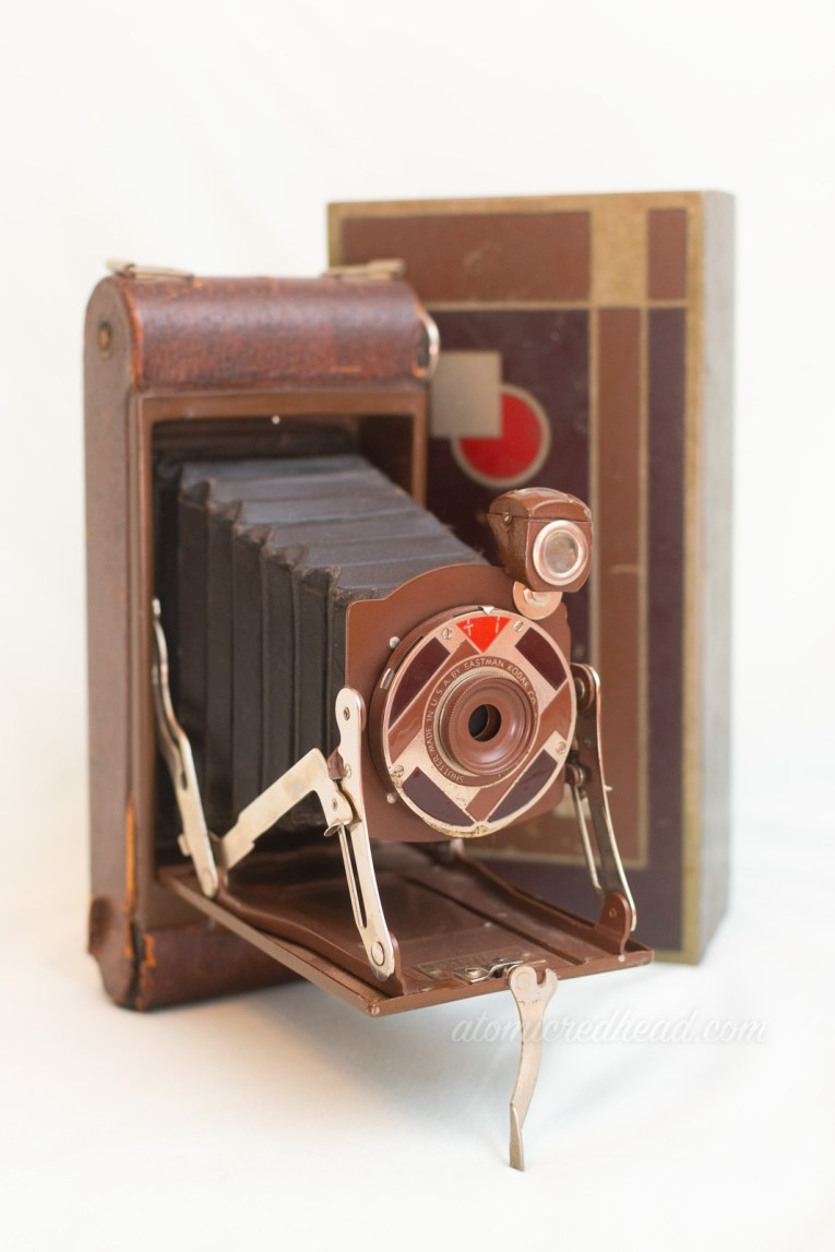 Kodak Gift Camera. A medium brown bellows style camera with a brown and red art deco style plate around the lens. The design is reflected on the lid of the box it came in which stands behind the camera.