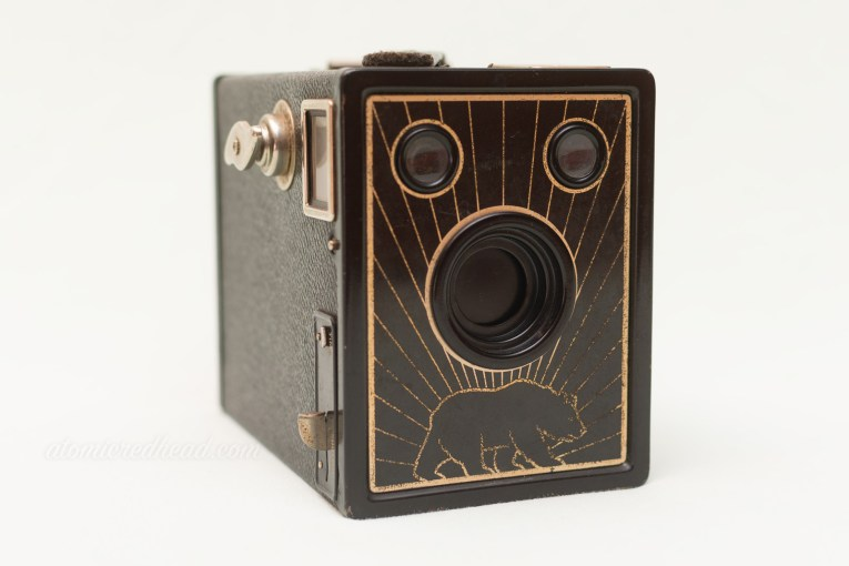 Bear Photo Special. A black box style camera with a metal faceplate that has a grizzly bear walking along the bottom with rays radiating from the bear.