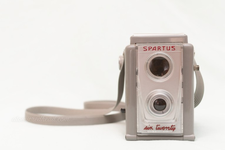 "Spartus Six-Twenty. A grey dual lens style camera. Red letters spell out ""Spartus Six-Twenty"""