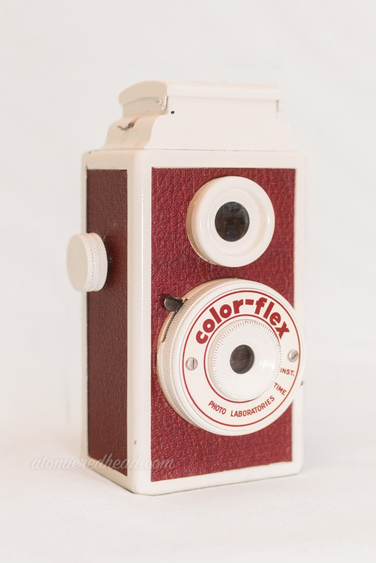 "Color-Flex. A maroon and cream dual lens camera. Text around the lower lens reads ""Color-Flex"""