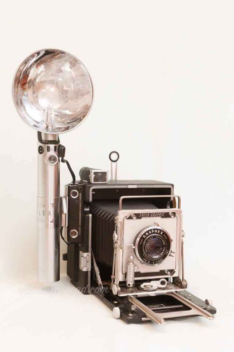 Graflex Pacemaker Speed Graphic. A large square bellows camera in black and silver. A large flash attachment is on the left.