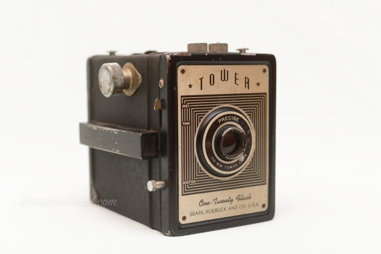 Tower One-Twenty Falsh. A black camera with a gold plate on the front.