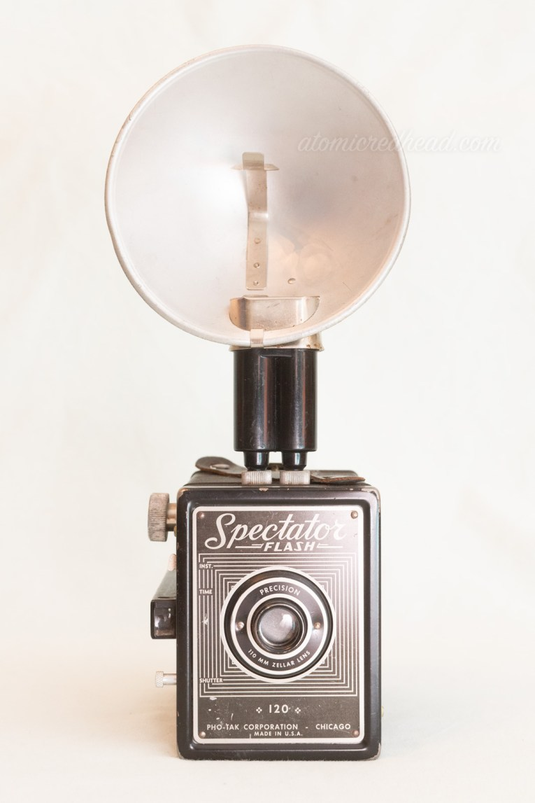Spectator Flash. A black square camera with a silver and black plate on the front. A flash attachment is on the top.