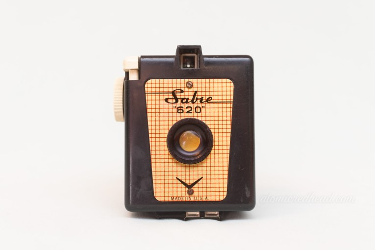 "Sabre 620. A black square camera with a gold plate on the front. Black script reads ""Sabre"""