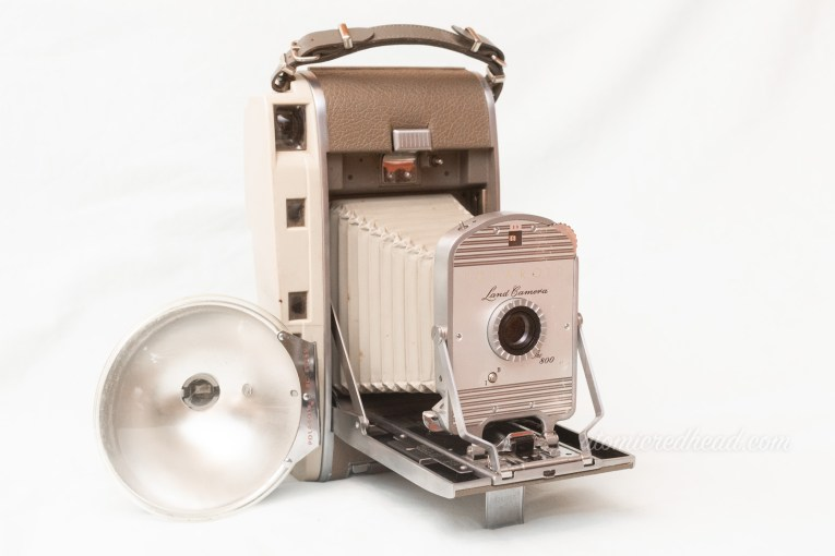 Polaroid Land Camera 800. A two tone grey camera with a bellows and a flash attachment.