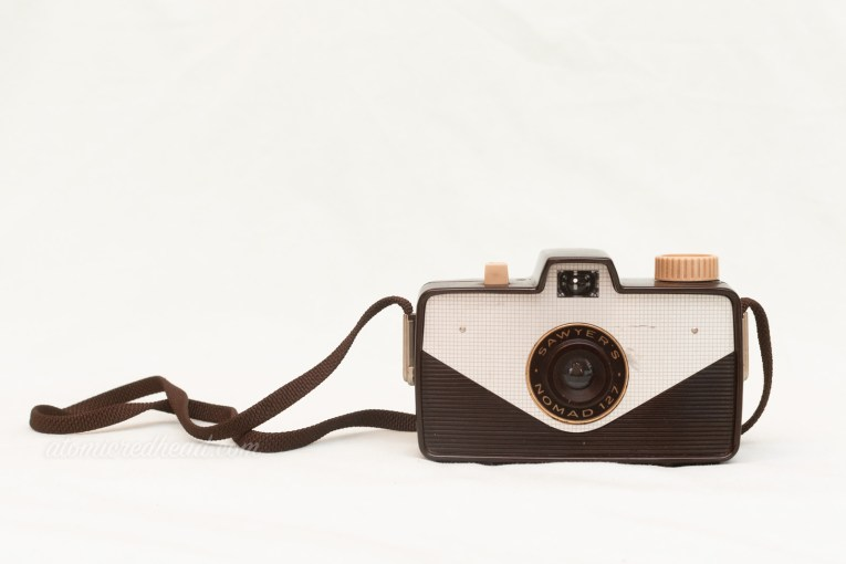 Sawyer Nomad 127. A rectangular brown camera with a triangular silver panel in front. The