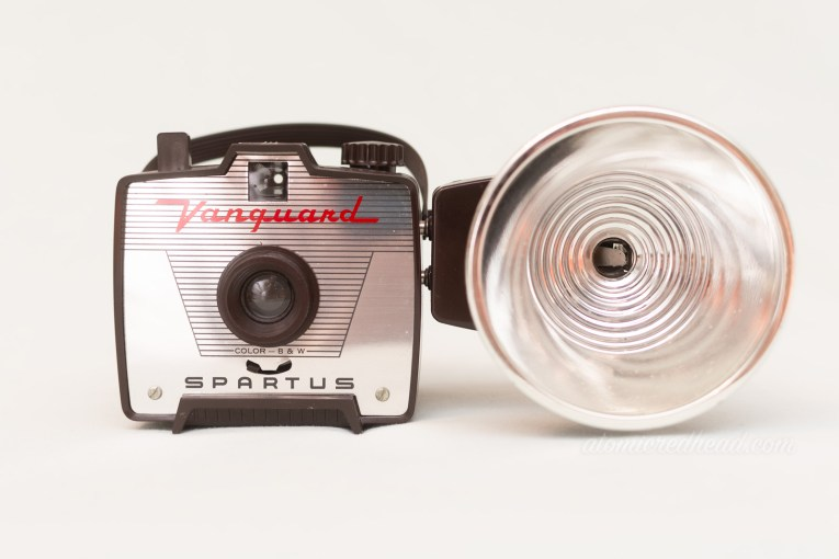 "Partus Vanguard. A small brown square camera with a silver plate on front, and red script reading ""Vanguard"" and a flash attachment on the right."