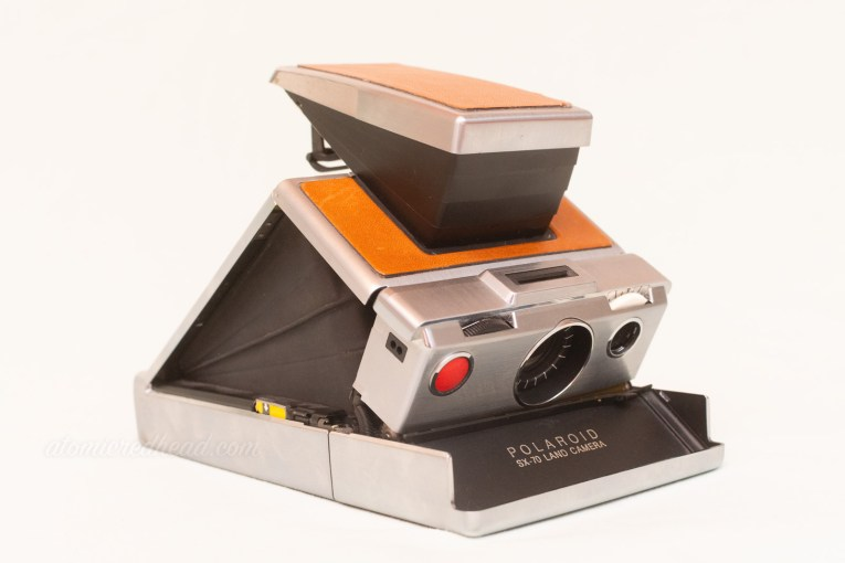 SX-70 Land Camera. The camera pops up like a tent. It features tan leather on the top and grey metal around the edges.