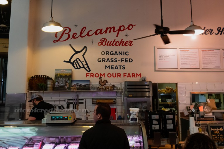 "Meat counter at Belcampo Butcher. The white wall is painted with red and black letters reading ""Belcampo Butcher Organic Grass-Fed Meats From Our Farm"""