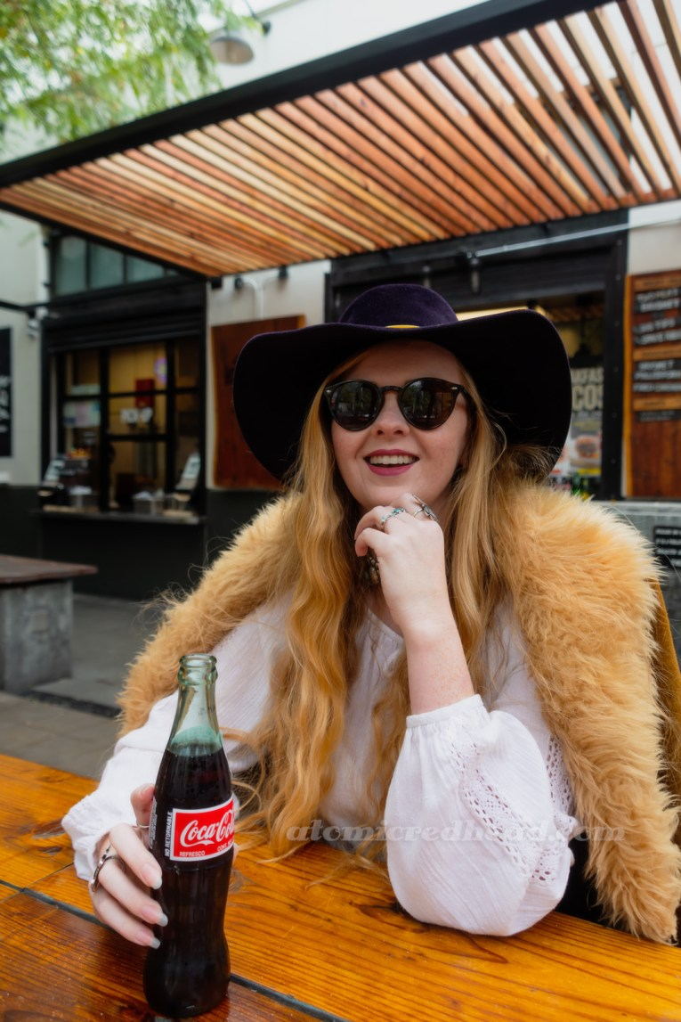 Myself, sitting at a table, wearing a dark blue velvet wide brim hat with a mustard band, and a light brown suede jacket with cream fur trim, a white peasant top underneath, holding a glass bottle of Coca-Cola
