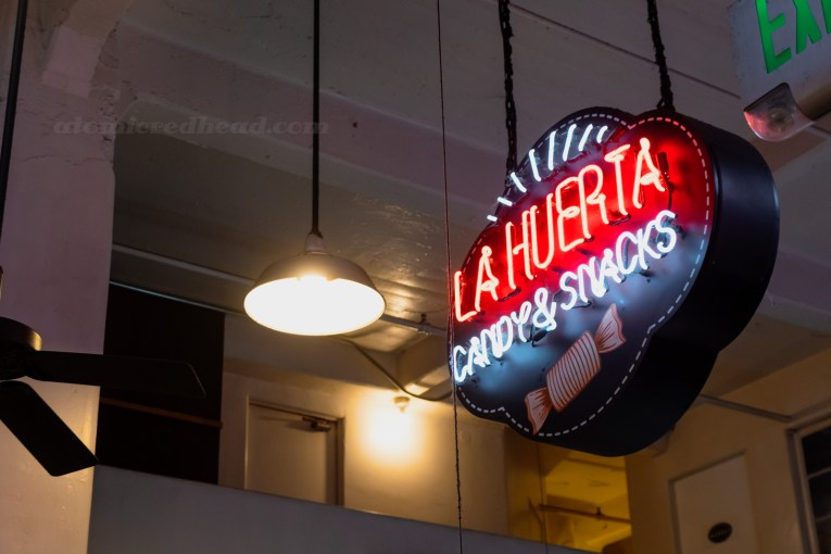 "A neon sign reads ""La Huerta Candy & Snacks"""