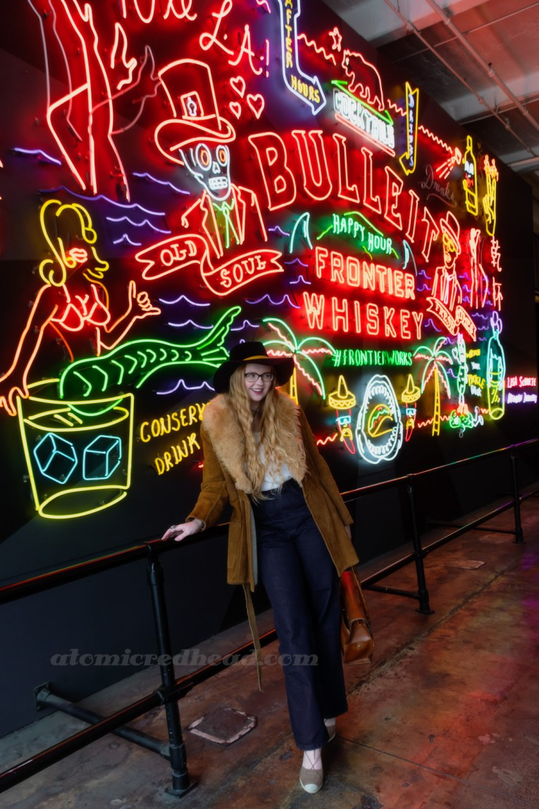 Myself, standing in front of the neon mural, wearing a dark blue velvet wide brim hat with a mustard band, and a light brown suede jacket with cream fur trim, a white peasant top underneath, and dark jeans.