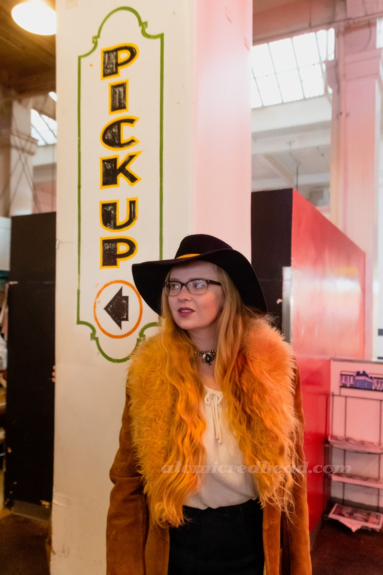 "Myself, leaning against a pillar that is hand painted with ""Pick up"" and an arrow, wearing a dark blue velvet wide brim hat with a mustard band, and a light brown suede jacket with cream fur trim, a white peasant top underneath"