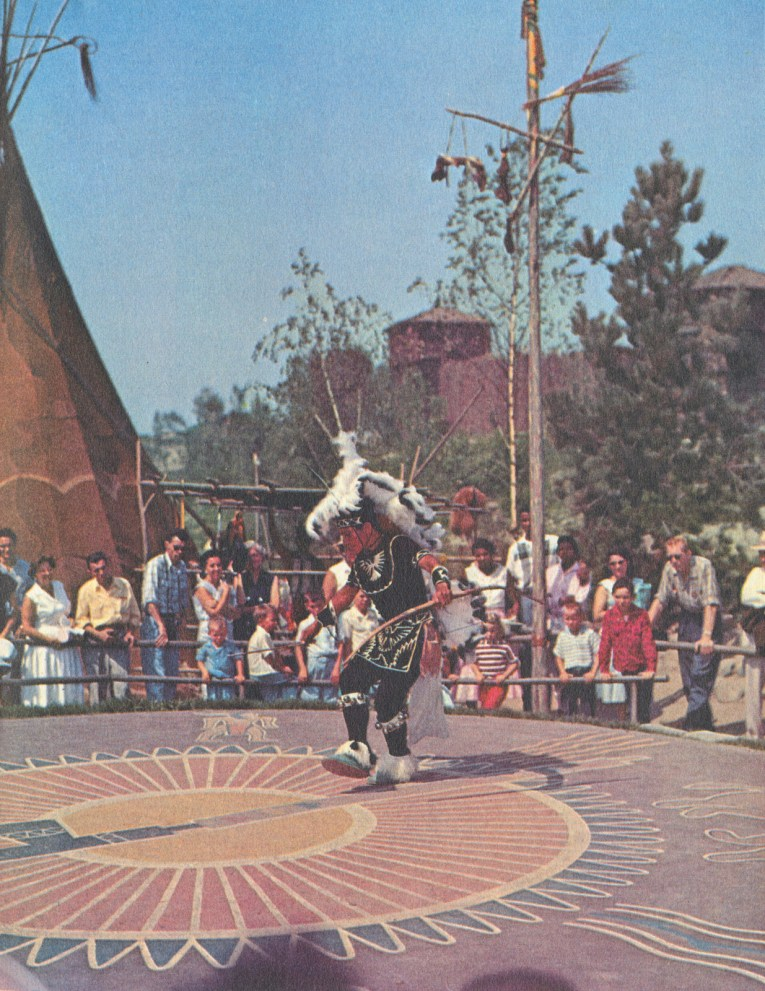 A photograph of a Native American dancer in a circle with Guests watching him.