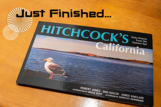"The book Hitchcock's California, which features an image of a bay on the cover with a seagull in the foreground. Text overlay at the top of the photo reads ""Just Finished..."""