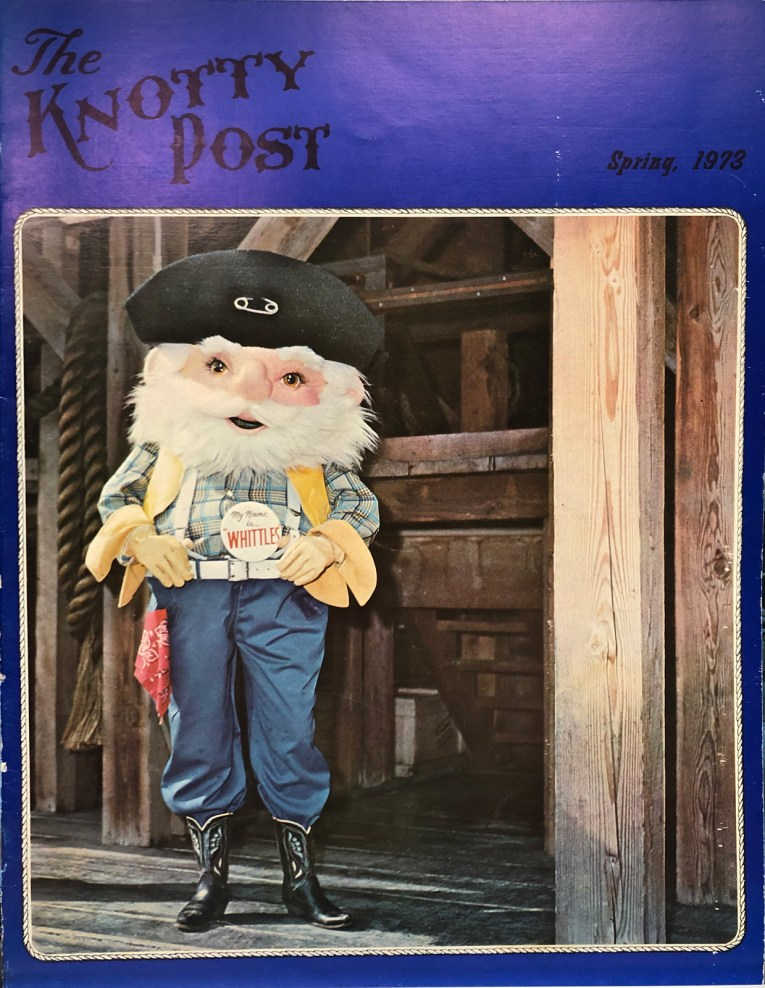 "The cover of The Knotty Post, Spring 1973. An awkwardly proportioned old miner in the form of a fuzzy mascot costume, he has a white beard, black hat, plaid shirt with yellow vest, and blue jeans. He wears a button reading ""My name is...Whittles'"""