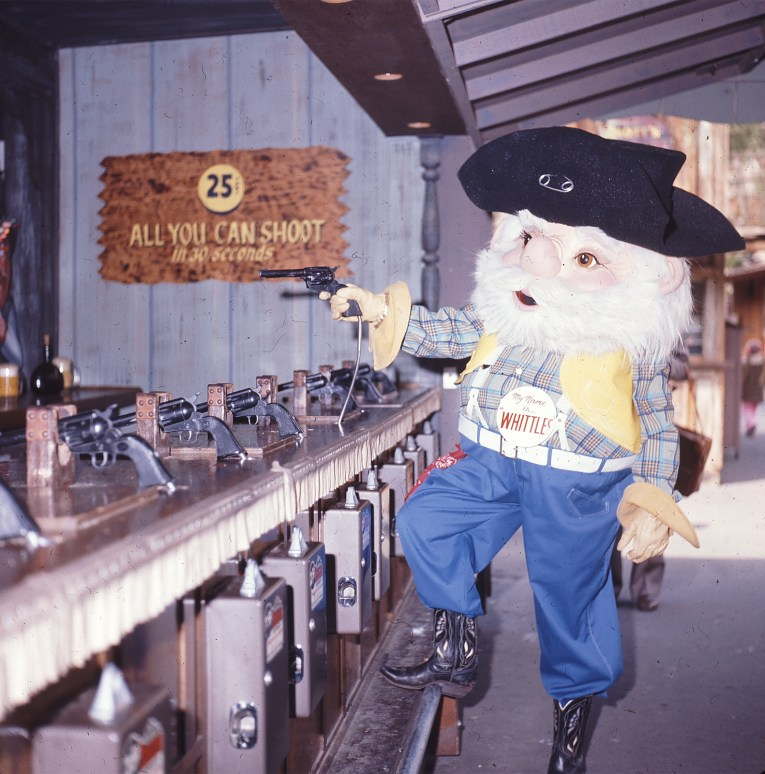 "An awkwardly proportioned old miner in the form of a fuzzy mascot costume, he has a white beard, black hat, plaid shirt with yellow vest, and blue jeans. He wears a button reading ""My name is...Whittles'"" stands at the Ghost Town Shooting Gallery."