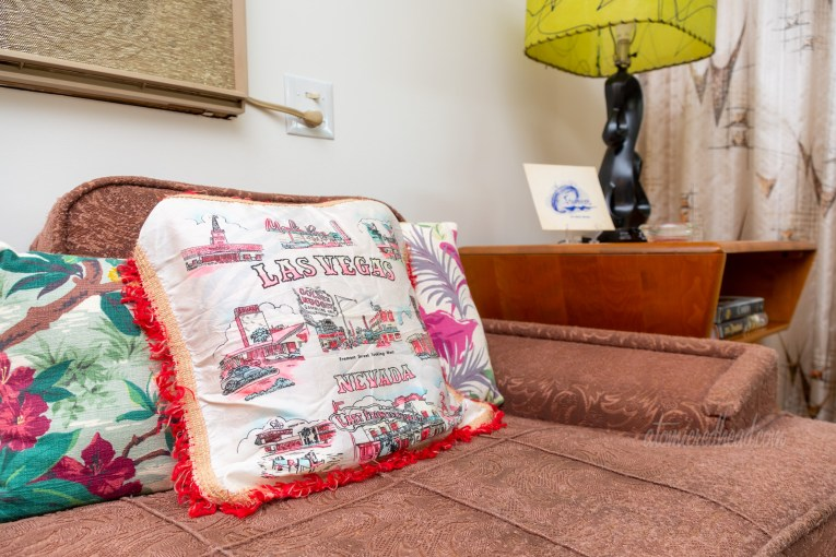 A souvenir pillow from Las Vegas sits on a vintage chair.