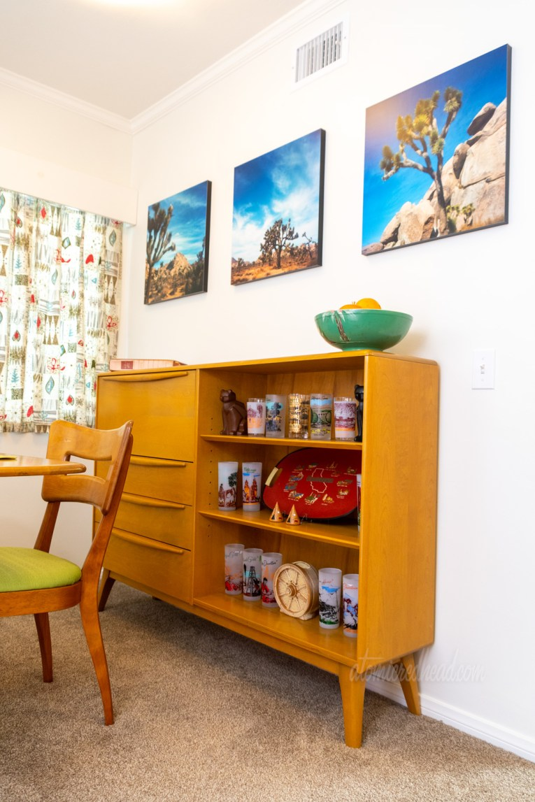 The secretary sits agains the back wall, with photos of Joshua Tree above. On the shelves of the secretary are vintage glasses featuring California icons.