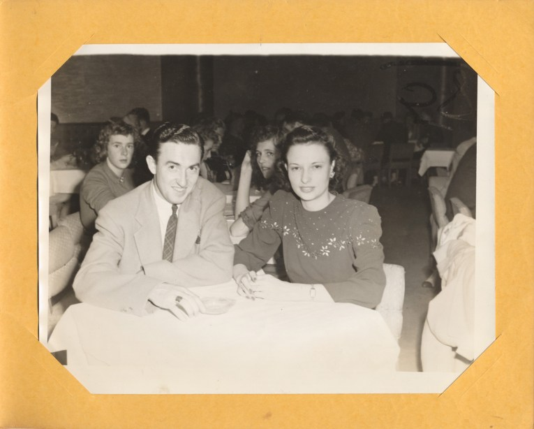 A couple sits at a table, smiling for the camera.