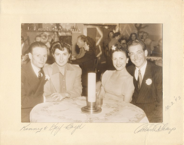 Two young couples sit at a table.