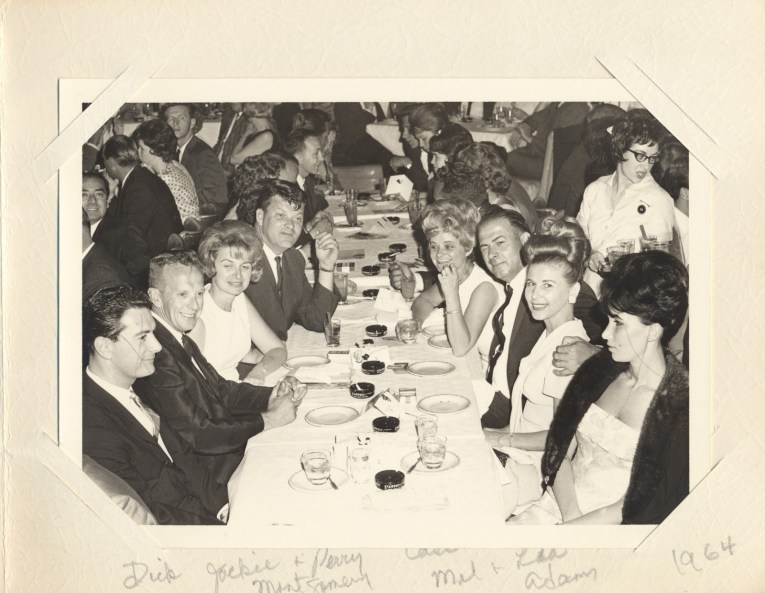 A large party is seated at a table, wearing formalwear.