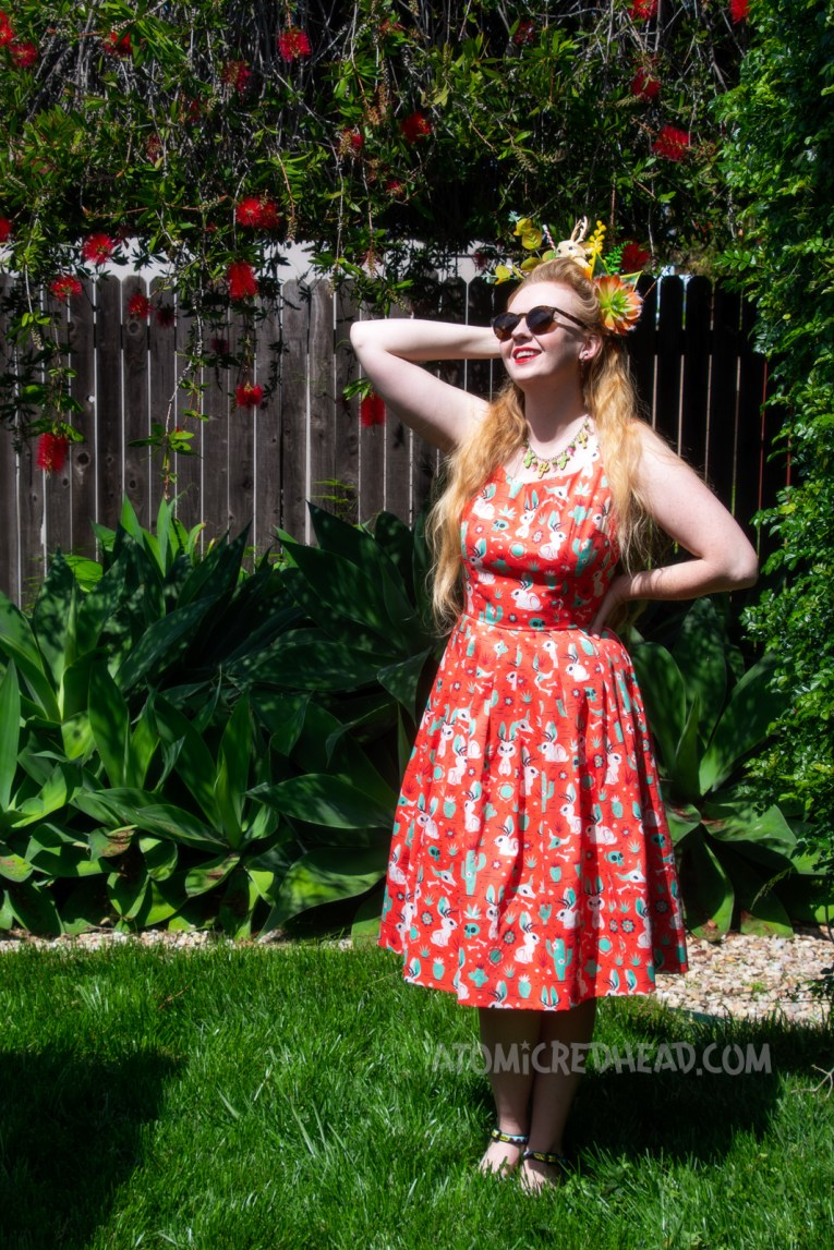 Myself wearing a crown made of fake succulents and a small cream jackalope, wearing a dress with a red, green, and cream print of cacti, jackalopes, and skulls, standing in our yard.
