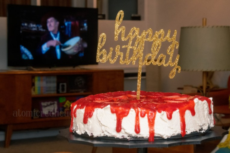 White cheesecake sits on a black cake stand. The Vincent Price film Theatre of Blood plays on the TV in the background.
