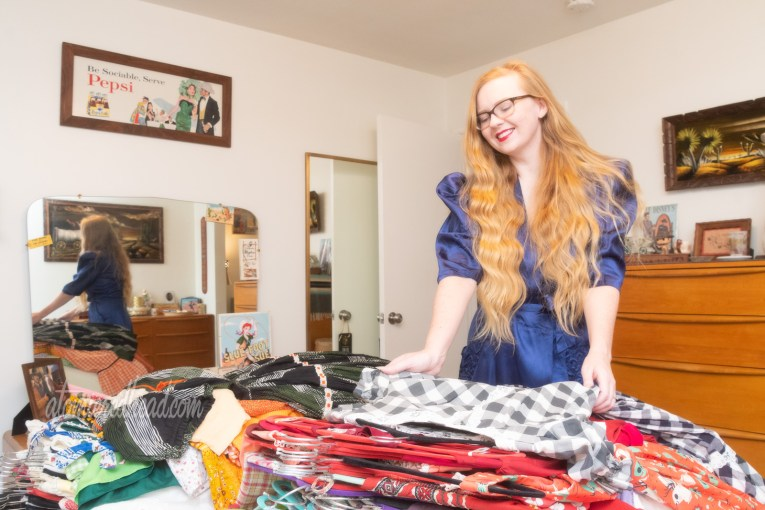 Myself, wearing a blue dressing gown, looking at the pile of clothes on my bed.