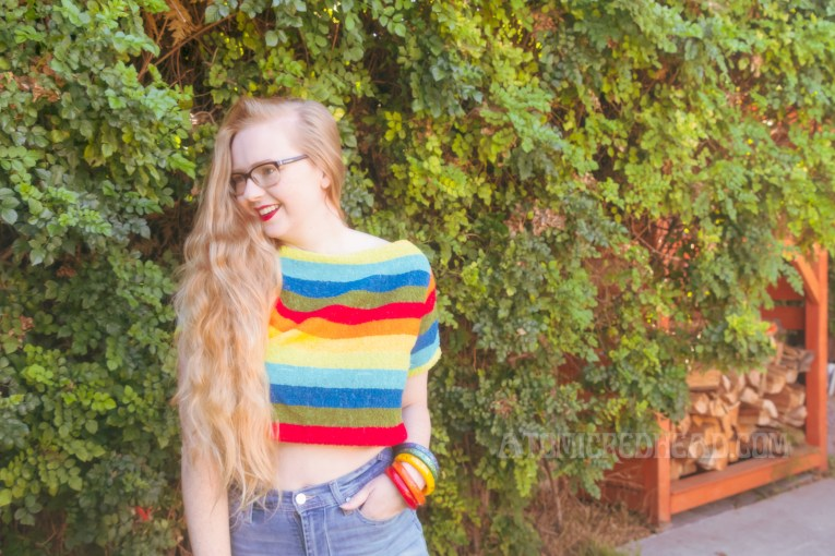 Myself wearing a rainbow striped shirt, cut off jean shorts, standing against a green bush. Match bangles that reflect the same colors of my shirt are on my left wrist.