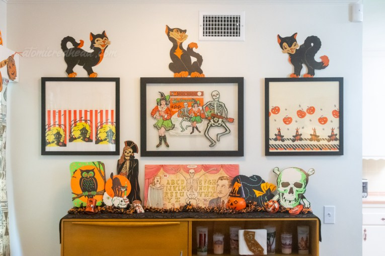 A buffet piece sits on the back wall of the dining room. Atop the buffet is a diecut owl, cat atop a skull, a skeleton wearing a pirate costume, in the middle a spirit board themed to the House on Haunted Hill, with a woman screaming, skeleton, and Vincent Price, to the right of it a plastic jack o'lantern with a black party hat with an orange cat atop it, and next to it a diecut skull. Hanging above all of it are themed framed pieces. On the left is a framed segment of a paper table cloth featuring an illustration of a haunted house. In the middle framed witch and skeleton, on the right a framed segment of a paper table cloth with witches and pumpkins. Sitting atop each frame is a diecut black cat.