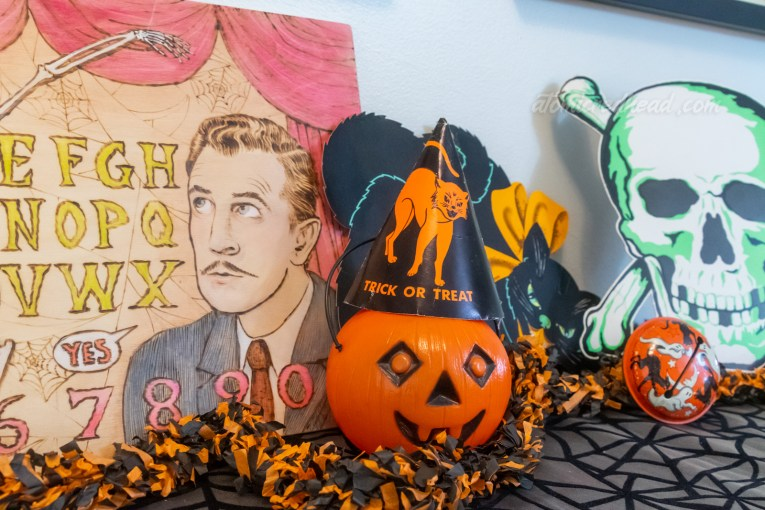 Close-up of part of the decor in the dining room, a spirit board that is themed to House on Haunted Hill, features Vincent Price's face, a small plastic jack o'lantern wears a black party hat with an orange cat on it, a black cat sits behind it, and a skull to the right of it.
