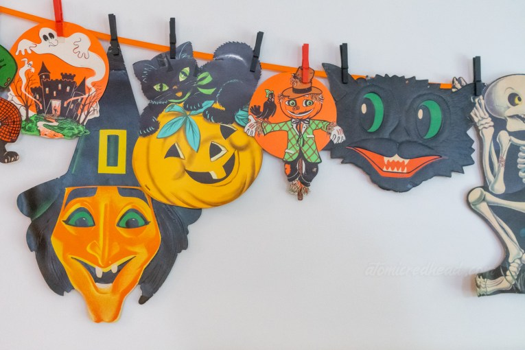 A grouping of diecut Halloween decorations clothes pinned to an orange ribbon, a ghost over a castle, a witch, a black cat atop a jack o'lantern, a scarecrow, and a black cat face.