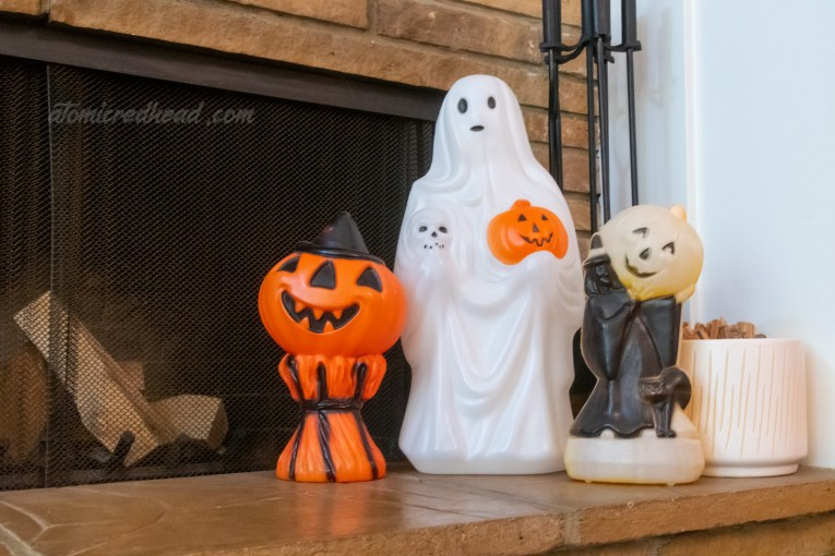 Trio of blowmolds on the hearth of the fireplace, a jack o'lantern on a stock of wheat, a ghost holding a skull and jack o'lantern, and a witch holding a jack o'lantern.