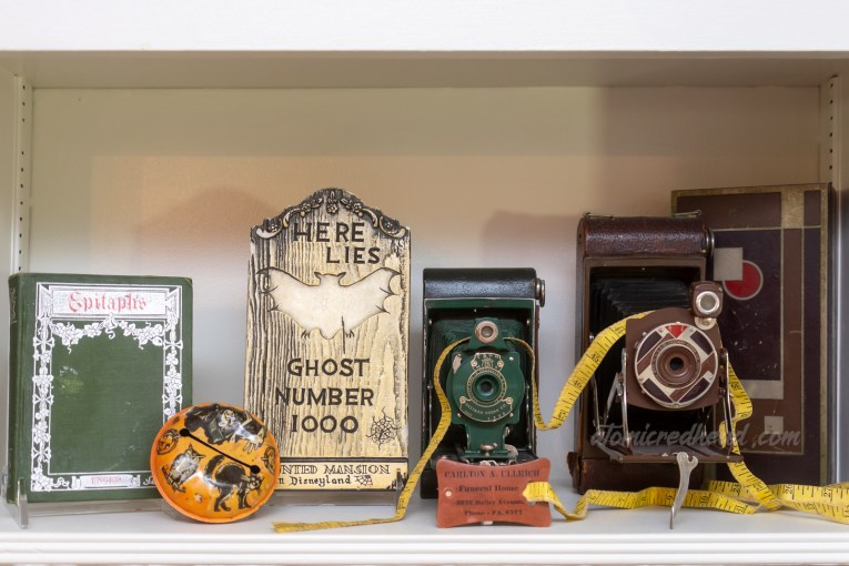 """Close-up of a shelf. On the right a small green book with silver gilding reads """"Epitaphs,"""" next to it is an orange and black noise maker with a black cat and a witch on it, next to it is a chalkware tombstone reading """"Here Lies Ghost Number 1000 Haunted Mansion Disneyland,"""" next to it is a green camera and next to it a brown camera. A tape measure winds through the cameras, and sits in front to read """"Carlton A. Ullrich Funeral Home."""""""