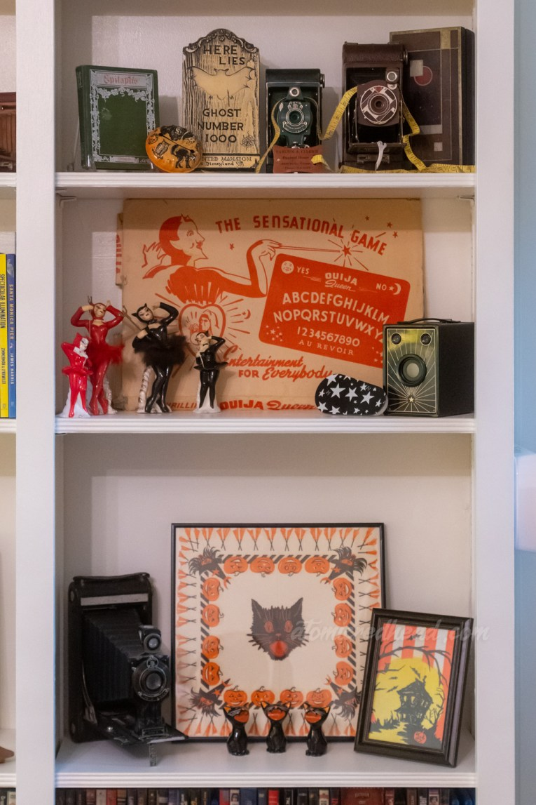 """A built in bookcase features various vintage cameras, a green book with the title """"Epitaphs"""" a tombstone reading """"Here Lies Ghost Number 1000"""" a small collection of ceramic dancers dressed as devils, and a framed napkin with witches, pumpkins, and broomsticks."""