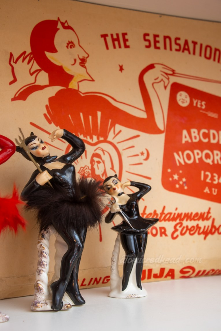 Two ceramic ballet dancers dressed in black devil attire.