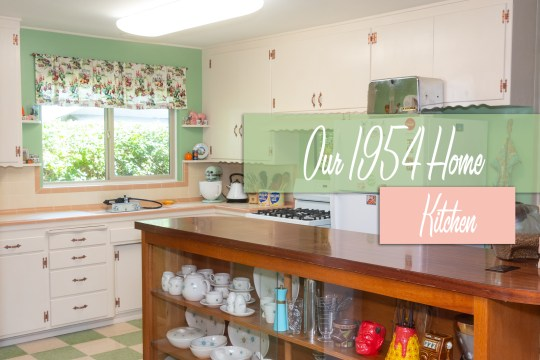 "Looking into our kitchen from the dining room. Cream and pink tile counter sits atop cream cabinets with copper hardware. Upper cabinets, also cream, sit against green walls. Text overlay reads ""Our 1954 Home Kitchen"""