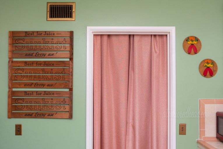 """Three wood crate sides hang on a green wall to the left of a doorway that has a pink curtain. Text on the crates reads """"Sunkist Best for Juice - and Every Use"""""""