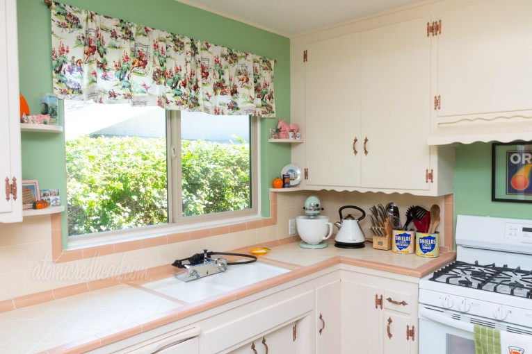 View toward the sink, which sits under a window. The window has a valance featuring cowboys near a campfire, roping steer, and yucca plants. The color scheme of the fabric is pink, green, and brown. A green Kitchenaid mixer sits in the corner.