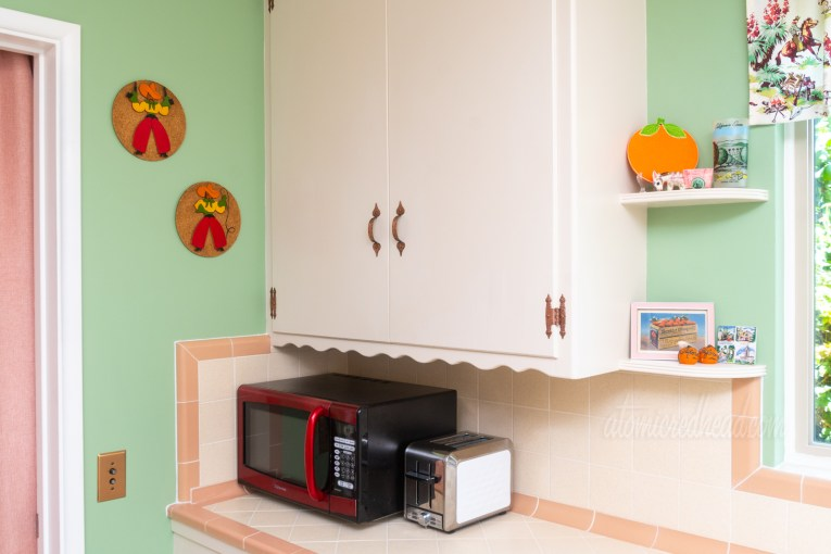 A red microwave rests on cream and pink tile counter. To the left and above the microwave are two circular pieces of art, cut wood cowboy and cowgirl that are mounted on cork.