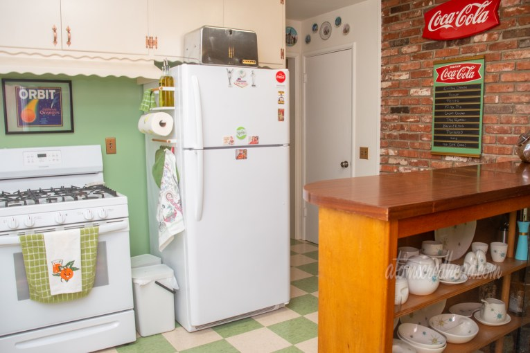 A white stove sits to the left of the fridge, just pas the fridge is a hallway with a doorway, next to the door a brick wall that has a Coca-Cola menu hanging on it. A bar with built in china hutch juts out from the right side.