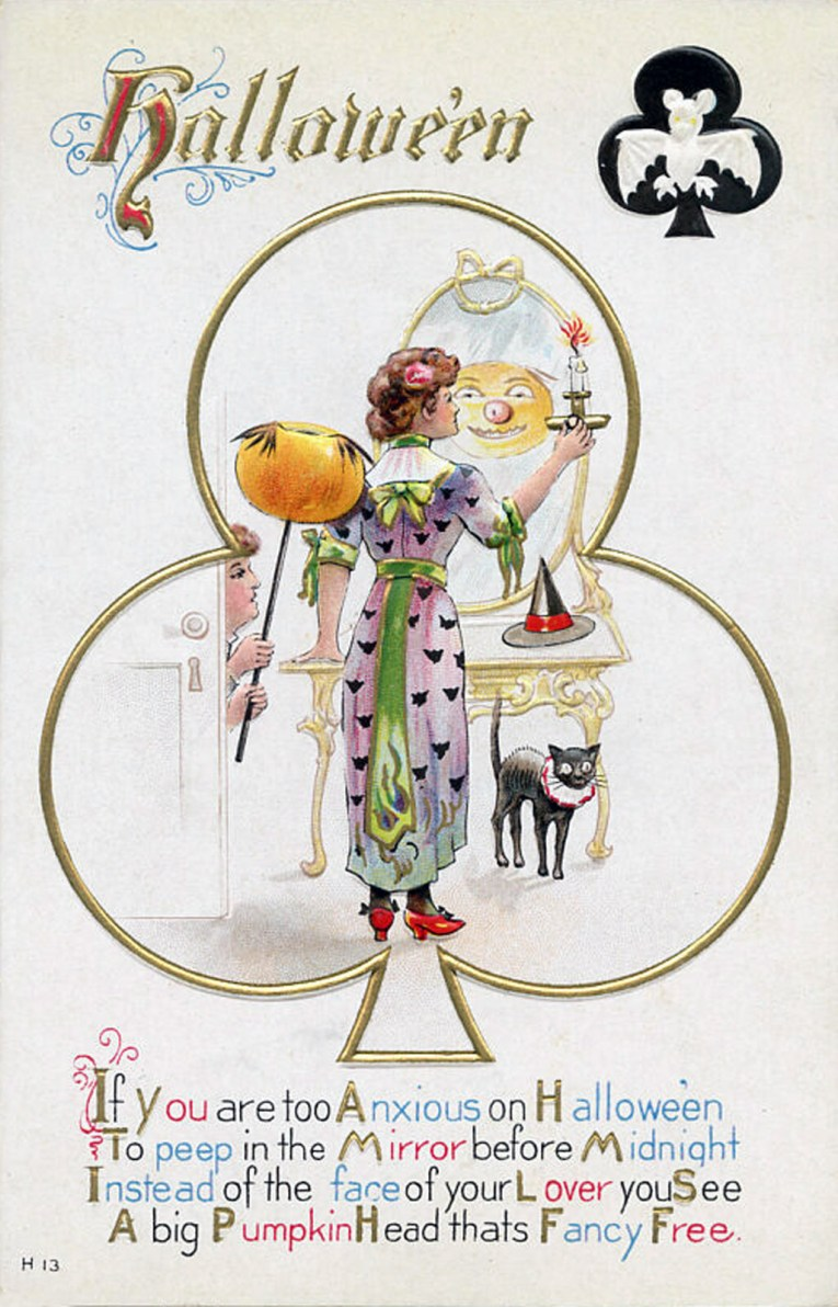 "A woman wearing a purple dress with green bows and little black bats on it holds a candle in front of a mirror. In the mirror is a funny pumpkin face, behind her a man holds a pumpkin on a stick. Text reads ""Halloween. If you are too Anxious on Halloween to peep in the mirror before midnight instead of the face of your lover you see, a big pumpkin head tats fancy free."""