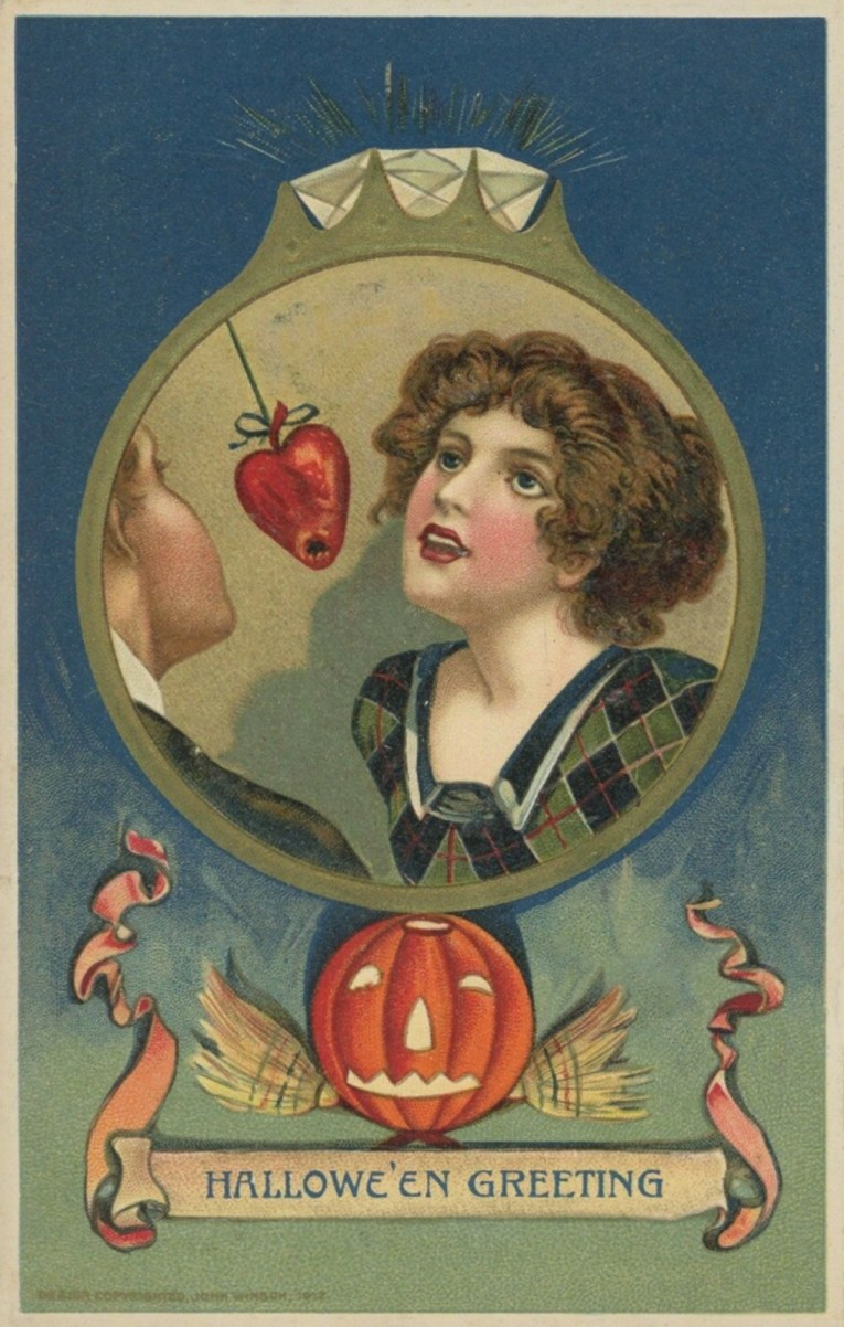 "Inside the circle of a diamond ring is a woman attempting to bite into an apple shaped like a heart. Text at the bottom reads ""Halloween Greeting"""