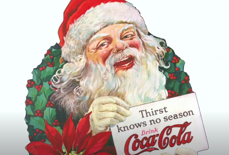 "Santa wearing a red hat with white fir trim emerges from a holly wreath holding a sign that reads ""Thirst knows no season Drink Coca-Cola."""
