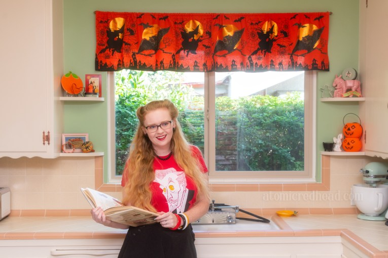 Myself, wearing a red shirt with an illustration of Vincent Price on it, holding a cookbook, standing in front of the sink in our kitchen. An orange valance hangs above the window, and features witches an owls. Shelves that flank the window have small pumpkins, a ghost, and cauldron.