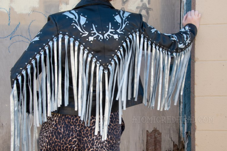 Close-up of the back of my jacket, which has a silver floral design at the top back and down the sleeves, along with cascading fringe across the sleeves andback.