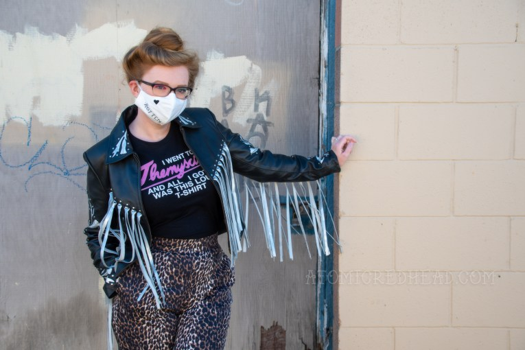 """Myself wearing a black and silver fringe leather jacket, black tee, and leopard print pants. I also wear a white face mask that has embroidered details of a heart and the word """"rotten"""" that emulates Harley Quinn's face tattoos."""