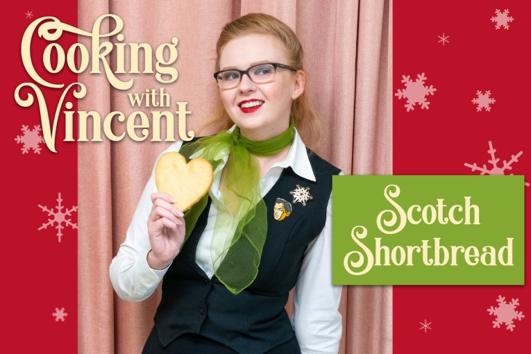 "Myself, wearing a white blouse, with a black vest over, a green chiffon scarf tied at my neck, pinned to the vest is a rhinestone snowflake brooch, and a pin of Vincent Price, in my hand is a heart shaped shortbread cookie. Overlaid text reads ""Cooking with Vincent Scotch Shortbread"""