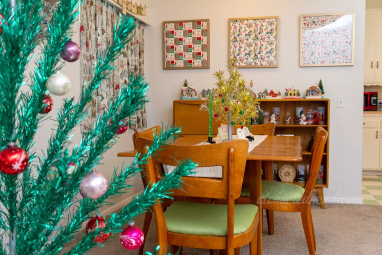 """A view into our dining room. Peeking from the left is our 6 foot green aluminum tree. In the middle of the dining room table is a short gold and silver aluminum tree. Hanging on the back wall are three squares of framed vintage wrapping paper. One reads """"Merry Christmas"""" repeatedly in script of gold, red, and green, the next features poodles, the third features Santa Claus. Atop the secretary are various small cardboard houses."""